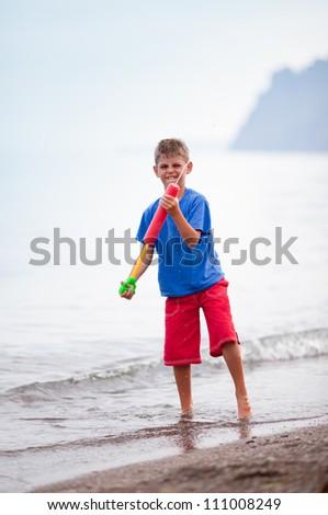 Boy playing with water gun - stock photo