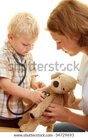 Boy plays at the podiatrist with a stethoscope - stock photo