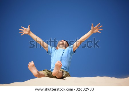 boy plays on the beach, hands and legs up