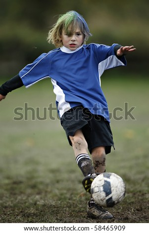 Boy plays soccer in a a blue shirt - stock photo