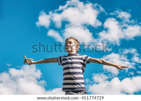 boy plays the pilot of the aircraft. boy holding a toy passenger plane and spread his arms wide for a flight on a background of blue sky - stock photo