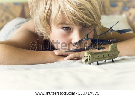 boy plays with a helicopter on the bed - stock photo
