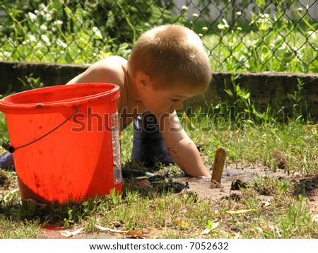 boy plays with toy tools in the garden - stock photo