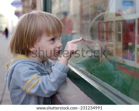 Boy pointing a favorite toy through the showcase                                          - stock photo