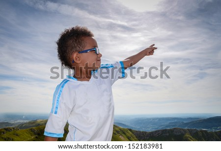 Boy pointing at sky with beautiful landscape - stock photo