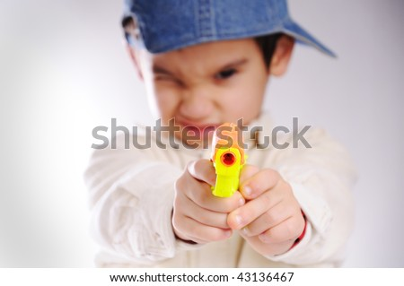 boy pointing gun at camera - stock photo
