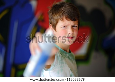 Boy pointing spray can with graffiti in the background. Focus on boy. - stock photo