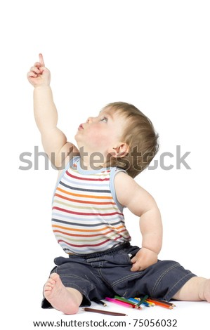 Boy pointing with his finger,  next to  some color pencils. Isolated. - stock photo