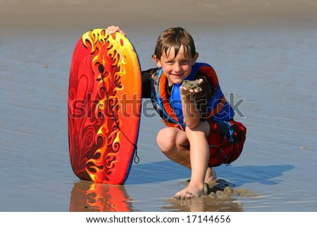 Boy posing with his body board - stock photo