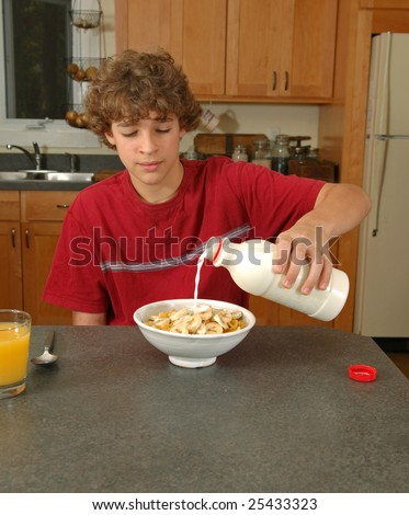 Boy pouring milk on cereal - stock photo