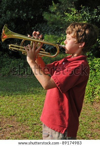boy practicing trumpet outdoors - stock photo