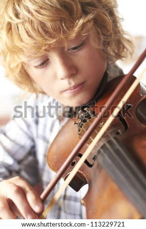 Boy Practicing Violin At Home - stock photo