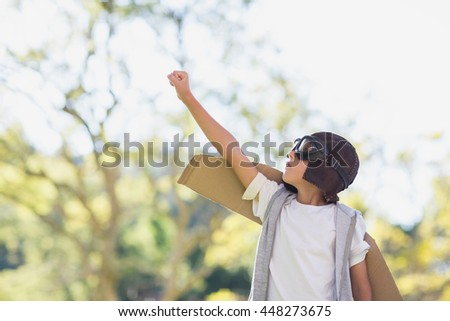 Boy pretending to be an aviation pilot in park - stock photo