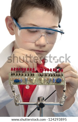 Boy probing a printed circuit board with volt meter probes while wearing safety glasses and a lab coat. - stock photo