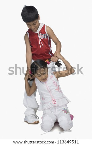 Boy pulling hair of his sister - stock photo
