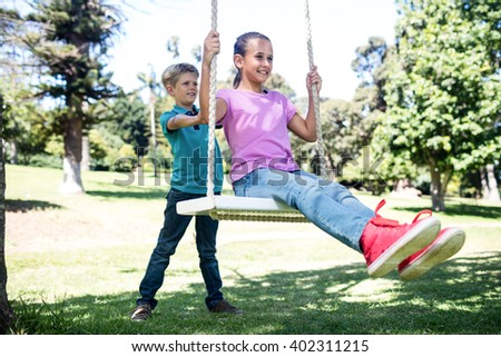 Boy pushing his sister on swing in park - stock photo