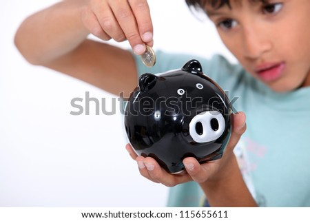 boy putting a coin into a money box - stock photo