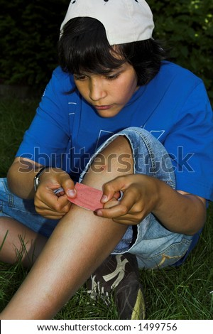 Boy putting band-aid on his knee - stock photo