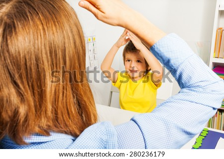 Boy putting hands together like therapist sitting - stock photo