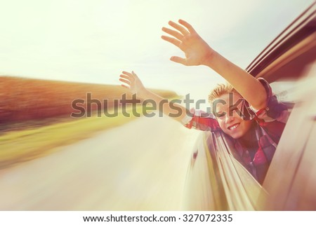 Boy putting his heads and hands out of the car window driving down a country road. Instagram effect. - stock photo
