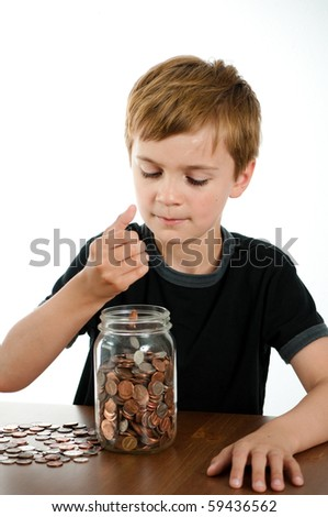 Boy Putting Money in Glass Jar - stock photo