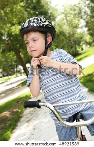 Boy putting on a bike helmet - stock photo