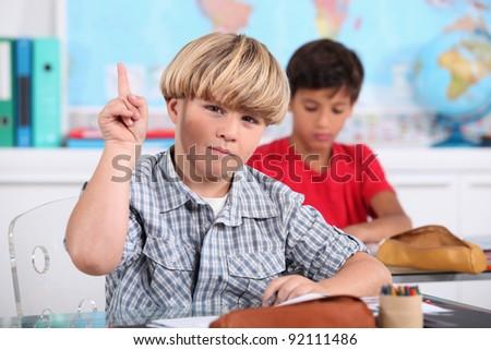 Boy raising his hand in class - stock photo