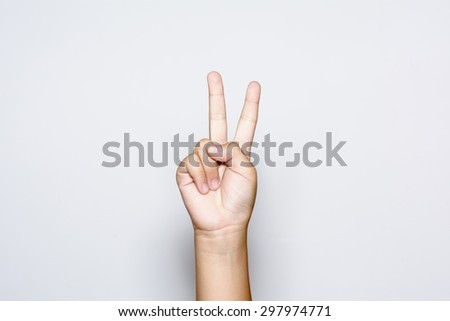 Boy raising two fingers up on hand it is shows peace strength fight or victory symbol and letter V in sign language on white background.  - stock photo