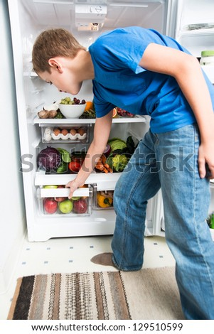 Boy Reaching for Apple in Refrigerator Full of Healthy Food Options - stock photo
