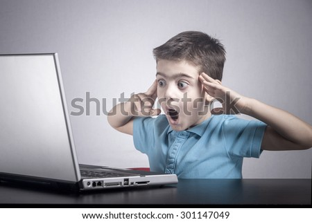 Boy reacts while using a laptop. Image cross processed for darker effect - stock photo