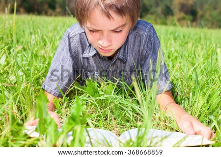 Boy reading a book laying on the sunny meadow in a summer park - stock photo