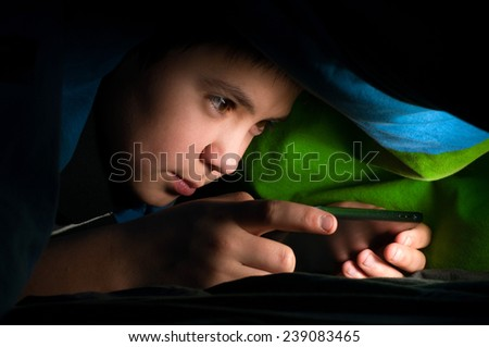 boy reading a book under the covers