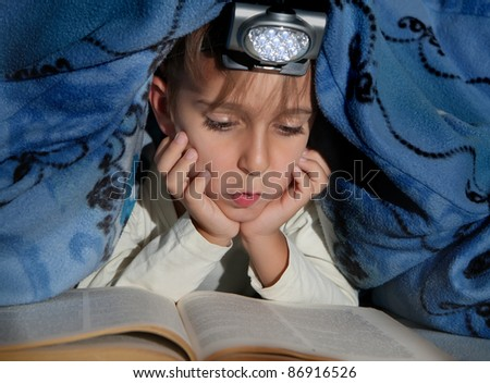 Boy reading a book under the covers with a flashlight