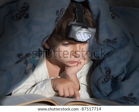 Boy reading a book under the covers with a flashlight - stock photo