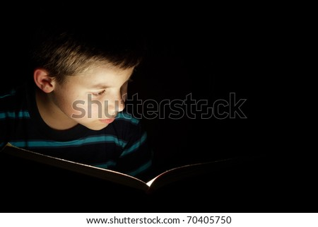 Boy reading bedtime story, dark photo, key light coming from book - stock photo