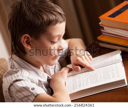 Boy reading book at home. Child education - stock photo