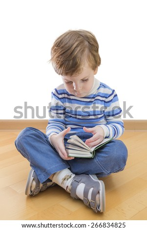 Boy reading book seating on the floor on white background - stock photo
