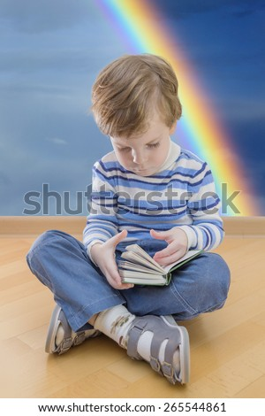 Boy reading book seating on the floor with rainbow in background - stock photo