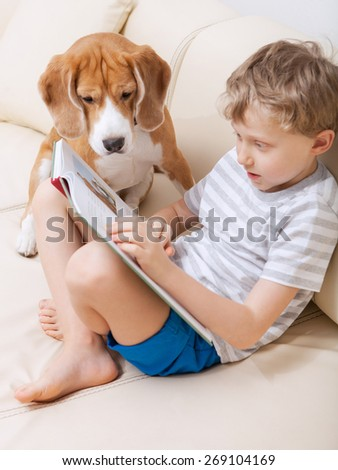Boy reading for his dog at home - stock photo