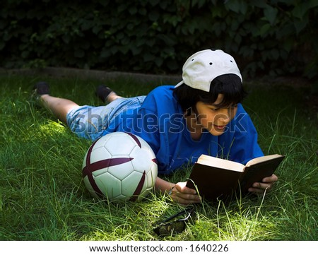 Boy reading in the park, next to his football - stock photo