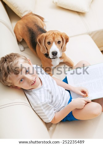 Boy reading tales for his dog at home - stock photo