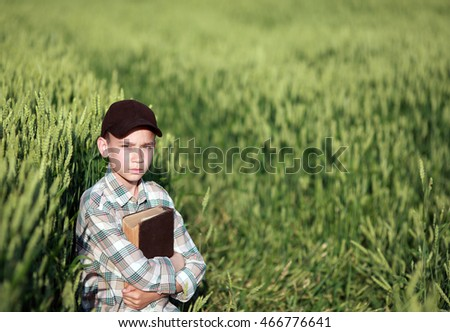 boy reads a book in a field of wheat