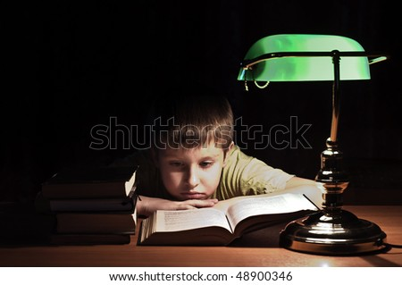 boy reads book in dark room under green lamp - stock photo