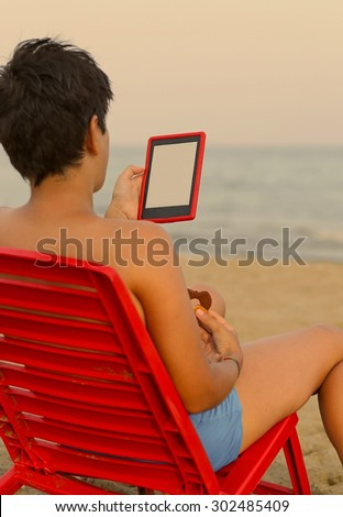 boy reads the ebook on the beach - stock photo