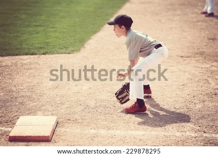 Boy ready at first base. Shallow focus - stock photo