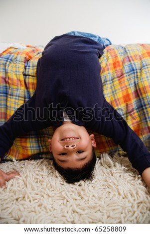 Boy reclining on bed - stock photo