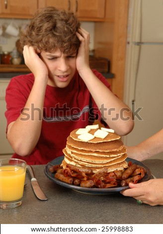 boy recoils in horror at enormous breakfast - stock photo