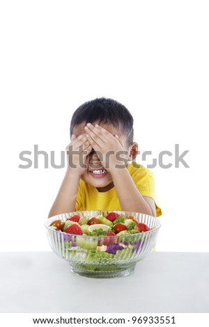 Boy refuses to eat salad by cover his eyes - stock photo