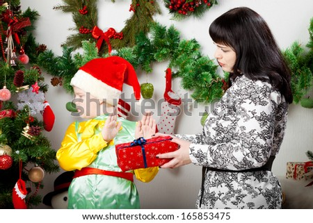 boy refusing Christmas gift box from mother - stock photo