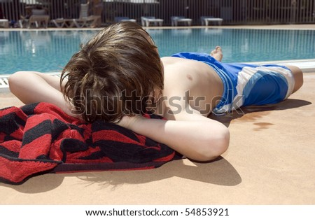 Boy relaxing at the poolside